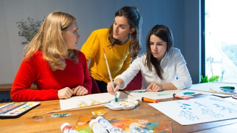 Art school student consulting drawing master during class. Two girls painting in studio, third one helping them with advice. Panting class concept
